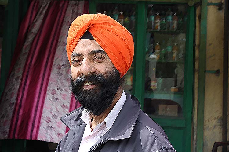 Sikh man in an orange turban is smiling in front of a green door