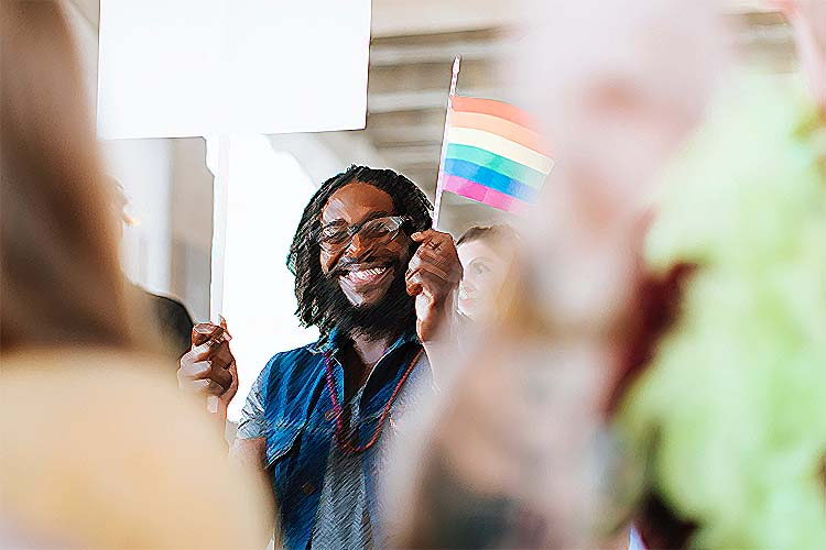A black man with dreads is smiling broadly, holding a pride flag