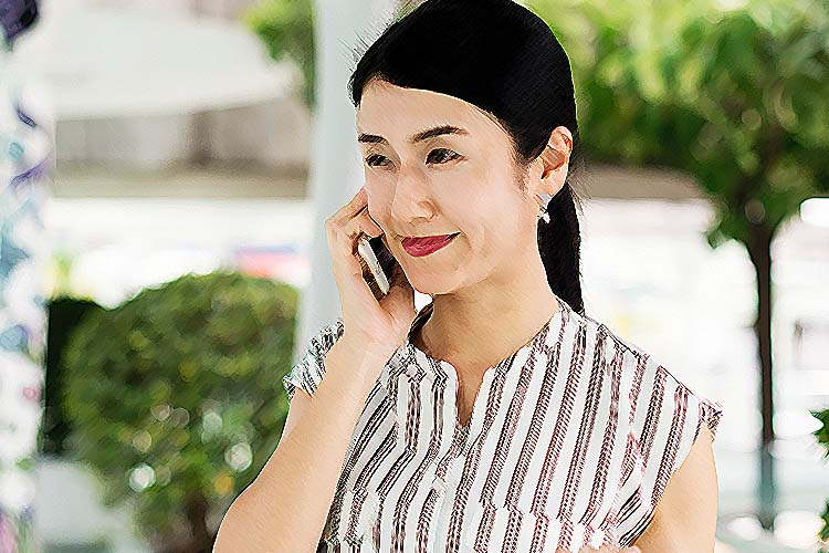 Asian woman wearing a pony tail is similing as she talks on the phone