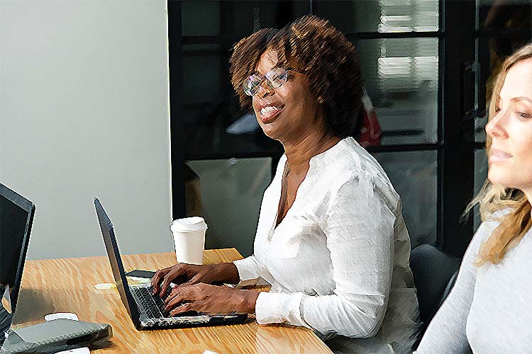 A Black woman with short, natural hair is looking up and smiling as she types on a laptop