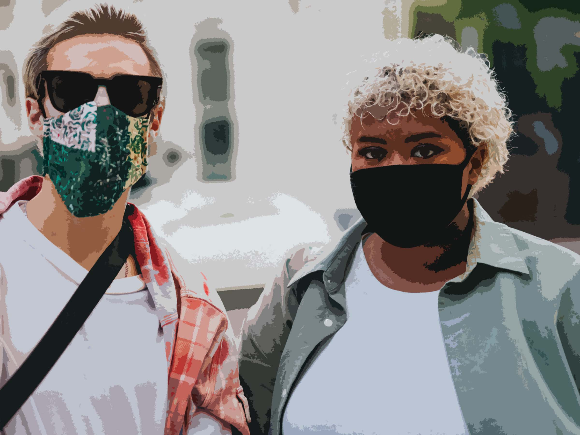 Two young people stand together wearing COVID-19 face masks. On the left is a White man and on the right is a Black woman